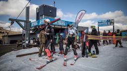 Pemain ski Alpine Afrika Selatan, Conner Wilson (kanan) bersiap untuk latihan sebelum berkompetisi di Olimpiade Musim Dingin 2018, Pegunungan Maluti, Kerajaan Lesotho, Selasa (10/7). (Marco Longari/AFP)
