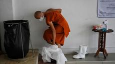 Seorang biksu melepas alat pelindung diri setelah melakukan kremasi untuk korban virus corona COVID-19 di Wat Chin Wararam Worawihan, Bangkok, Thailand, 30 Juli 2021. Kasus COVID-19 di Thailand kini tengah melonjak. (Lillian SUWANRUMPHA/AFP)