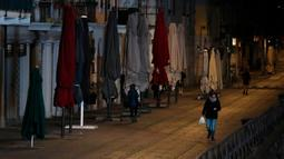 Beberapa orang berjalan di Kanal Naviglio Grande, Milan, Italia, Selasa (10/3/2020). Bar-bar yang biasa berjajar di sepanjang Kanal Naviglio Grande terlihat tutup menyusul dektrit lockdown yang berlaku di Italia demi mencegah penyebaran virus corona (COVID-19). (AP Photo/Antonio Calanni)