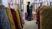 Pekerja menata bahan kain dagangan di Pasar Tanah Abang, Jakarta, Kamis (1/4/2021). Kemenperin ingin meningkatkan daya saing industri Tekstil dan Produk Tekstil (TPT) nasional, salah satunya dengan berupaya mengurangi ketergantungan terhadap bahan baku tekstil impor. (Liputan6.com/Johan Tallo)