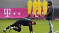 Kiper Bayern Munchen Manuel Neuer (kiri) melakukan pemanasan dekat pelatih Hansi Flick saat sesi latihan di Munich, Jerman, Selasa (10/12/2019). Bayern Munchen akan menghadapi Tottenham Hotspur pada pertandingan Grup B Liga Champions. (Christof STACHE/AFP)