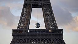 Sebuah bola besar tergantung disela Menara Eiffel, Perancis, (26/11). Karya seni ' Earth Crisis ' oleh seniman Amerika Shepard Fairey ditampilkan karena Paris menjadi tuan rumah Konferensi Perubahan Iklim Dunia 2015 (COP21). (REUTERS/Charles Platiau)