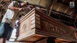 Pekerja menyelesaikan pembuatan peti mati di Jalan Bouraq, Tangerang, Banten, Minggu (4/11). Harga per peti dijual mulai dari 5 juta hingga 15 juta rupiah sesuai dengan ukuran kayu yang diinginkan. (Liputan6.com/Johan Tallo)