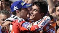 Pebalap Repsol Honda, Marc Marquez, bersama pebalap Ducati, Jorge Lorenzo, merayakan kemenangan pada GP Aragon di Sirkuit Motorland, Alcaniz, Minggu (24/9/2017). Marquez berhasil finis tercepat dengan waktu 42 menit 6,819 detik. (AFP/Jose Jordan)