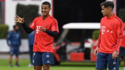 Pemain Bayern Munchen, Philippe Coutinho, berdiskusi dengan Thiago Alcantara saat latihan perdananya di Munchen, Selasa (20/8). Bintang Brasil ini didatangkan dari Barcelona. (AFP/Christof Stache)
