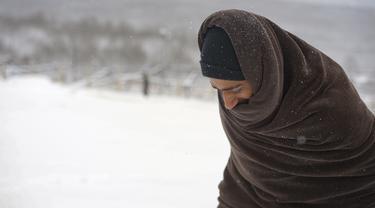 Seorang migran dengan dibungkus selimut berjalan melewati salju di kamp Lipa, barat daya Bosnia, dekat perbatasan dengan Kroasia, Sabtu (26/12/2020). Ratusan migran terdampar di tenda-tenda kumuh dan terbakar di Bosnia, di tengah hujan salju yang lebat dan suhu membeku. (AP Photo/Kemal Softic)