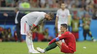 Bintang Portugal, Cristiano Ronaldo, dijatuhkan oleh bek Spanyol, Sergio Ramos, pada laga Grup B Piala Dunia di Stadion Fisht, Sochi, Jumat (15/6/2018). Kedua negara bermain imbang 3-3. (AP/Sergei Grits)