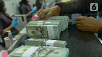 Aktivitas penukaran uang dolar AS di gerai penukaran mata uang asing PT Ayu Masagung, Jakarta, Kamis (19/3/2020). Nilai tukar Rupiah pada Kamis (19/3) sore ini bergerak melemah menjadi 15.912 per dolar Amerika Serikat, menyentuh level terlemah sejak krisis 1998. (merdeka.com/Imam Buhori)