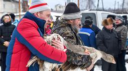 Dua pria membawa angsa mereka selama pertarungan angsa tradisional di desa Kalikino sekitar 450 km di luar Moskow, Rusia (17/3). (AFP Photo/Vasily Maximov)