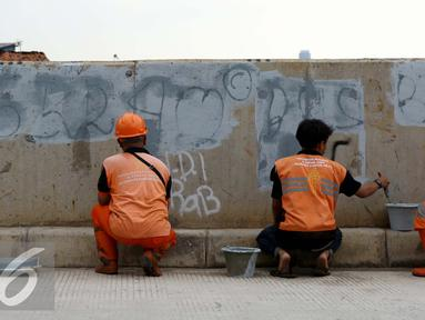 Petugas Pekerja Penanganan Sarana dan Prasarana Umum (PPSU) mengecat tembok yang penuh dengan vandalisme di sepanjang sisi tanggul Kali Ciliwung, Jakarta, Selasa (11/10). (Liputan6.com/Gempur M Surya)