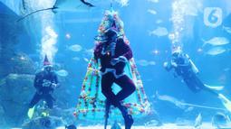Penyelam berkostum sinterklas meyapa pengunjung di dalam air yang dihias pohon natal di Jakarta Aquarium dan Safari, Mal Neo Soho, Grogol, Jakarta, Kamis (24/12/2020). Pertunjukan ini menerapkan protokol kesehatan yang ketat untuk mencegah penularan Covid-19. (Liputan6.com/Angga Yuniar)