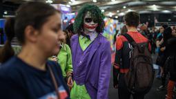 Seorang cosplayer berkostum ala karakter The Joker berjalan melalui kerumunan orang dalam acara Comic Con Africa di Johannesburg, Sabtu (21/9/2019). Comic Con Africa untuk tahun kedua di benua itu  akan berlangsung selama empat hari dari 21 hingga 24 September. (Michele Spatari/AFP)