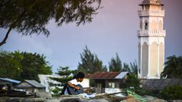 Seorang pria memainkan gitar sambil menikmati matahari terbenam di pantai di Banda Aceh (7/4). Sebagai pusat pemerintahan, Banda Aceh menjadi pusat kegiatan ekonomi, politik, sosial dan budaya. (AFP Photo/Chaideer Mahyuddin)