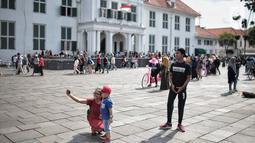 Pengunjung foto di depan Museum Sejarah Kota Tua, Jakarta, Kamis (27/12). Kawasan wisata Kota Tua dipadati wisatawan dari dalam kota maupun luar kota Jakarta selama libur sekolah. (Liputan6.com/Faizal Fanani)