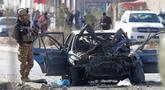 Seorang tentara berdiri di samping kendaraan yang rusak setelah serangan bom mobil di Kabul, Afghanistan (13/11/2019). Setidaknya tujuh orang tewas dan tujuh lainnya luka-luka ketika sebuah bom mobil meledak pada jam sibuk pagi hari Kabul pada 13 November. (AFP/STR)