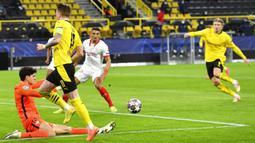 Pemain Borussia Dortmund Marco Reus mengoper bola ke Erling Haaland saat menghadapi Sevilla FC pada pertandingan leg kedua babak 16 besar Liga Champions di Dortmund, Jerman, Selasa (9/3/2021). Laga berakhir imbang 2-2. (Bernd Thissen/Pool via AP)