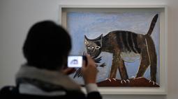 Pengunjung mengambil gambar lukisan berjudul Chat saisissant un oiseau karya Pablo Picasso dalam pameran 'Guernica' di Museum Picasso, Paris, Prancis, Jumat (23/3). Pameran didedikasikan untuk lukisan luar biasa Pablo Picasso. (AP Photo/Christophe Ena)