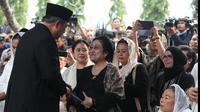Presiden ke-6 RI Susilo Bambang Yudhoyono bersalaman dengan Presiden ke-5 RI Megawati Soekarnoputri usai prosesi pemakaman Ani Yudhoyono di TMP Kalibata, Jakarta, Minggu (2/6/2019). Megawati duduk bersebelahan dengan Ibu Negara Iriana Joko Widodo dan Sinta Nuriyah Wahid. (Liputan6.com/HO/Rangga)