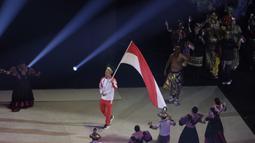 Atlet polo air, Ridjkie Mulia, membawa bendera saat kontingen Indonesia melintas pada upacara pembukaan SEA Games 2019 di Philipine Arena Bulacan, Manila, Sabtu (30/11). Pesta olahraga se-Asia Tenggara ini akan berlangsung hingga 11 Desember. (Bola.com/M