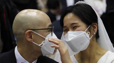 Pasangan memakai masker mengikuti kegiatan nikah massal di Cheong Shim Peace World Center di Gapyeong, Korea Selatan, Jumat, (7/2/2020). Meski memakai masker untuk mencegah virus corona, para pasangan pengantin tampak bahagia di acara tersebut. (AP Photo/Ahn Young-joon)