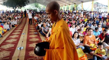Seorang biksu berjalan di depan umat Buddha yang merayakan Hari Raya Waisak 2562 BE/2018 di Wihara Ekayana Arama, Jakarta Barat, Selasa (29/5). Puja Bakti Massal Waisak 2562 BE diikuti oleh ribuan umat Buddha. (Liputan6.com/JohanTallo)