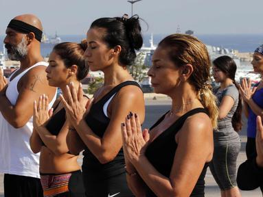 """Warga Lebanon melakukan gerakan yoga selama acara """"108 Sun Salutations"""" di ibukota Martir Beirut (22/10). (AFP Photo/Anwar Amro)"""