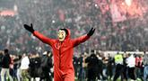 Suporter Olympiakos turun ke lapangan merayakan kemenangan atas AC Milan pada laga Europa di Stadion Georgios Karaiskakis, Athena, Kamis (13/12). Olympiakos menang 3-1 atas AC Milan. (AFP/Aris Messinis)