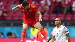 Pemain Denmark Martin Braithwaite (kanan) menyaksikan pemain Wales Ben Davies melompat untuk merebut bola pada pertandingan babak 16 besar Euro 2020 di Johan Cruyff Arena, Amsterdam, Belanda, Sabtu (26/6/2021). Denmark menang 4-0. (AP Photo/Peter Dejong, Pool)