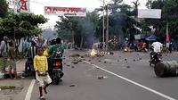 Massa turun ke jalan dalam unjuk rasa yang berujung kerusuhan di Manokwari, Papua, Senin (19/8/2019). Mereka membakar gedung DPR juga memblokade jalan dengan membakar ban sebagai buntut dari peristiwa yang dialami mahasiswa Papua di Surabaya dan Malang, serta Semarang beberapa hari lalu. (STR / AFP)