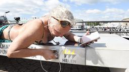 Lena Salmi mengisi baterai ponselnya saat berjemur di bangku panel surya di Helsinki, Finlandia, (9/7). Bangku dapat digunakan untuk mengisi daya perangkat bahkan ketika matahari tidak bersinar. (AFP Photo/Lehtikuva/Martti Kainulainen)