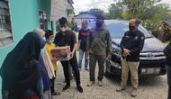 Wartawan membagikan mi instan dan sembako ke penghuni panti asuhan disaksikan Kabid Humas Polda Riau. (Liputan6.com/M Syukur)