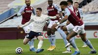 Pemain Manchester City, Phil Foden, melepaskan tendangan saat melawan Aston Villa pada laga Liga Inggris di Stadion Villa Park, Rabu (21/4/2021). City menang dengan skor 2-1. (Carl Recine/Pool via AP)