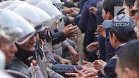 Massa dari Badan Eksekutif Mahasiswa Seluruh Indonesia (BEM SI) bersalaman dengan polisi saat aksi unjuk rasa di sekitar DPR RI, Jakarta, Selasa (1/10/2019). Selain berorasi secara damai, para mahasiswa membagikan bunga untuk para polisi yang mengawal aksi mereka. (Liputan6.com/Immanuel Antonius)