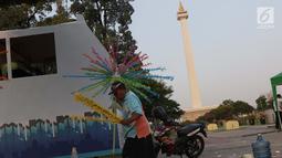 Pekerja menyelesaikan pembuatan kembang hiasan untuk diletakkan di atas kendaraan hias di kawasan Monas, Jakarta, Jumat (28/6/2019). Kendaraan hias tersebut dipersiapkan untuk Jakarnaval 2019 yang menjadi  perayaan HUT ke-492 DKI Jakarta, Minggu (30/6). (Liputan6.com/Helmi Fithriansyah)