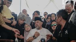 Komedian Indro Warkop menenangkan anaknya saat pemakaman istrinya, Nita Octobijanthy di TPU Tanah Kusir, Jakarta, Rabu (10/10). Nita meninggalkan tiga orang anak. (Liputan6.com/Faizal Fanani)