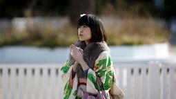Seorang gadis Jepang berpakaian kimono berdoa saat perayaan Coming of Age Day (Hari Kedewasaan Nasional) di taman hiburan di Tokyo, Senin (11/1). Hari Kedewasaan Nasional ini dirayakan para muda-mudi yang menginjak usia 20 tahun. (REUTERS/Yuya Shino)