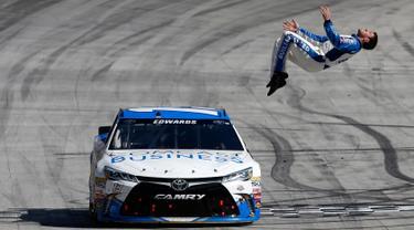 Pembalap Carl Edwards melakukan aksi gila dengan salto dari mobil ketika mesin dalam keadaan berjalan perlahan usai merayakan kemenangan NASCAR Sprint Cup Series Food City 500 di Bristol Motor Speedway (17/4). (AFP/Matt Sullivan)