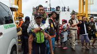 Petugas menggendong pengungsi usai turun dari kapal ferry di Pelabuhan Bakauheni, Lampung (26/12). Aktivitas gunung berapi anak Krakatau yang mengakibatkan gelombang tsunami 22 Desember lalu memaksa belasan ribu orang mengungsi. (AFP Photo/Mohd Rasfan)