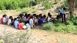 Para pelajar Yaman yang terlantar menghadiri kelas di bawah pohon sebuah lapangan terbuka, di distrik Abs utara, Yaman pada 28 Oktober 2018. UNICEF menyebut sekitar dua juta anak di Yaman putus sekolah, sejak konflik melanda pada 2015. (ESSA AHMED/AFP)