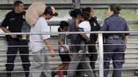 Imigran ilegal dikawal untuk pulang kembali ke negara asalnya oleh petugas imigrasi Amerika Serikat (AP/David J. Philip)