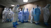 Petugas medis antre untuk melepas jas pelindung sebelum pulang kerja di Rumah Sakit Palang Merah di Wuhan pada 28 Februari 2020. Jumlah korban meninggal akibat virus corona (Covid-19) di seluruh dunia hingga Minggu (8/3) pagi sudah mencapai 3.570 orang, terbanyak masih di China. (STR/AFP)