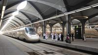 Para penumpang berjalan di peron ketika kereta api kecepatan tinggi Haramain resmi beroperasi di stasiun kereta Makkah, Kamis (11/10). Pengoperasian perdana kereta Haramain membawa jamaah dan musafir lainnya dari Makkah ke Madinah. (BANDAR ALDANDANI/AFP)