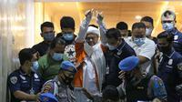 M Rizieq Shihab (tengah) digiring petugas saat meninggalkan gedung Ditreskrimum Polda Metro Jaya, Jakarta, Minggu dini hari (13/12/2020). Rizieq Shihab ditahan setelah menjalani pemeriksaan sebagai tersangka penghasutan dan kerumunan di tengah pandemi COVID-19. (Liputan6.com/Helmi Fithriansyah)