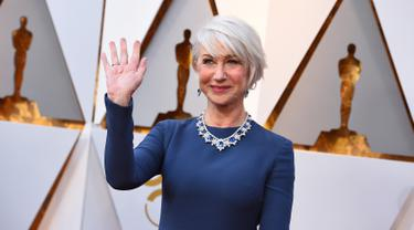 Aktris senior Helen Mirren melambaikan tangannya saat berpose di karpet merah Piala Oscar 2018 atau Academy Award ke-90, Los Angeles, Minggu (4/3). Di usia 71, Helen Mirren masih enerjik dan cantik di atas karpet. (Jordan Strauss/Invision/AP)