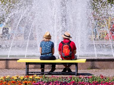 Pengunjung bersantai di depan air mancur di pameran hortikultura EGA (Erfurt Garden Construction Exhibition) di Erfurt, Jerman, Kamis (19/4). Masyarakat Jerman banyak memilih bersantai di taman saat musim semi. (AP Photo/Jens Meyer)