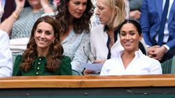 Ekspresi Duchess of Cambridge Kate Middleton (kiri) dan Duchess of Sussex Meghan Markle saat menyaksikan pertandingan final tunggal putri Wimbledon 2019 antara Serena Williams dengan Simona Halep di All England Lawn Tennis and Croquet Club, London, Inggris, Sabtu (13/7/2019). (BEN CURTIS/POOL/AFP)