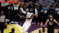 Pemain LeBron James, LeBron James memasukkan bola saat timnya bertanding dengan tim Stephen dalam pertandingan basket NBA All Star di Los Angeles, Amerika Serikat, Minggu (18/2). LeBron James meraih Most Valuable Player (MVP). (AP Photo/Alex Gallardo)
