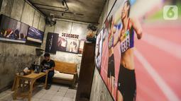 Pengunjung menikmati kopi sambil bekerja di kedai Ngopi di Halaman Jalan Pulo Kamboja, Kebayoran Lama, Jakarta, Selasa (12/01/2021). Kedai yang menawarkan konsep galeri foto dan sejumlah koleksi buku fotografi bisa menginspirasi pengunjung yang datang sambil nongkrong. (Liputan6.com/Fery Pradolo)