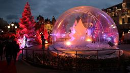 Orang-orang mengunjungi bola kaca raksasa dan dekorasi untuk menyambut Natal yang menghiasi depan Kasino Monte-Carlo di Monako pada 7 Desember 2018. (Photo by VALERY HACHE / AFP)