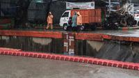 Sejumlah petugas memeriksa ketinggian air Pintu Air Manggarai, Jakarta, Senin (5/2). Warga di sekitaran Sungai Ciliwung diimbau untuk terus waspada akan tingginya limpahan air. (Liputan6.com/Faizal Fanani)